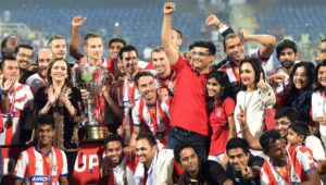 Atletico de Kolkata players and management team celebrate with the ISL trophy in 2014. Picture:PTI