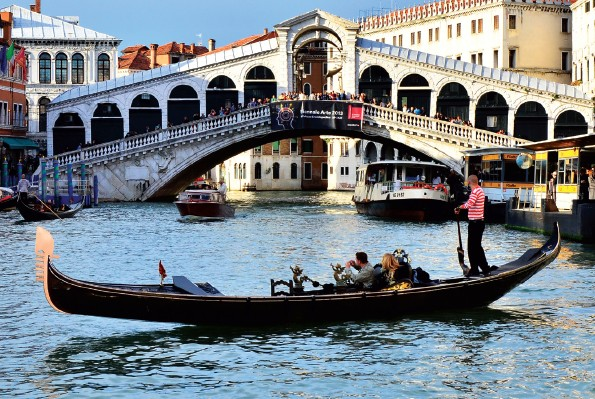 Tourists cruising on a gondola in front of the oldest bridge of Venice - the Rialto bridge