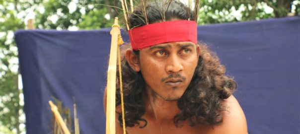 A tribal theatre actor enacting a hunting scene in the Tepantar theatre village