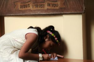 A kid at the Mother House writing a prayer