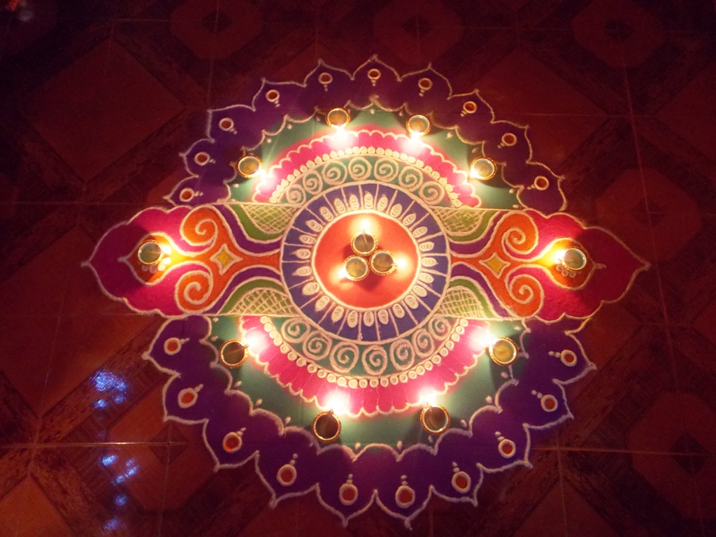 A rangoli pattern made with powdered colours and diyas