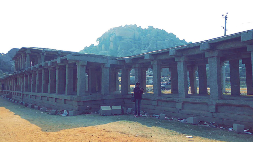 A photographer is trying to capture one of the many structures in Hampi