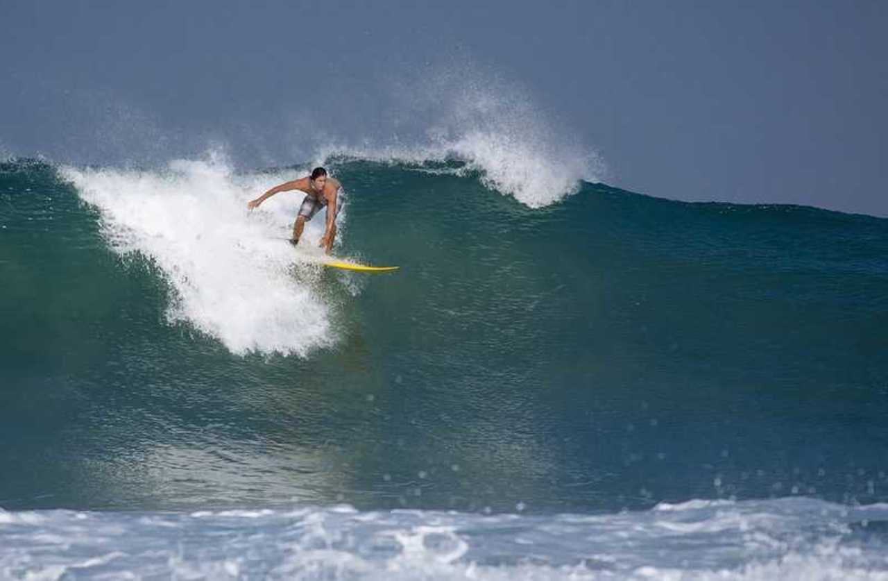 A professional surfer rides the waves at Paradip