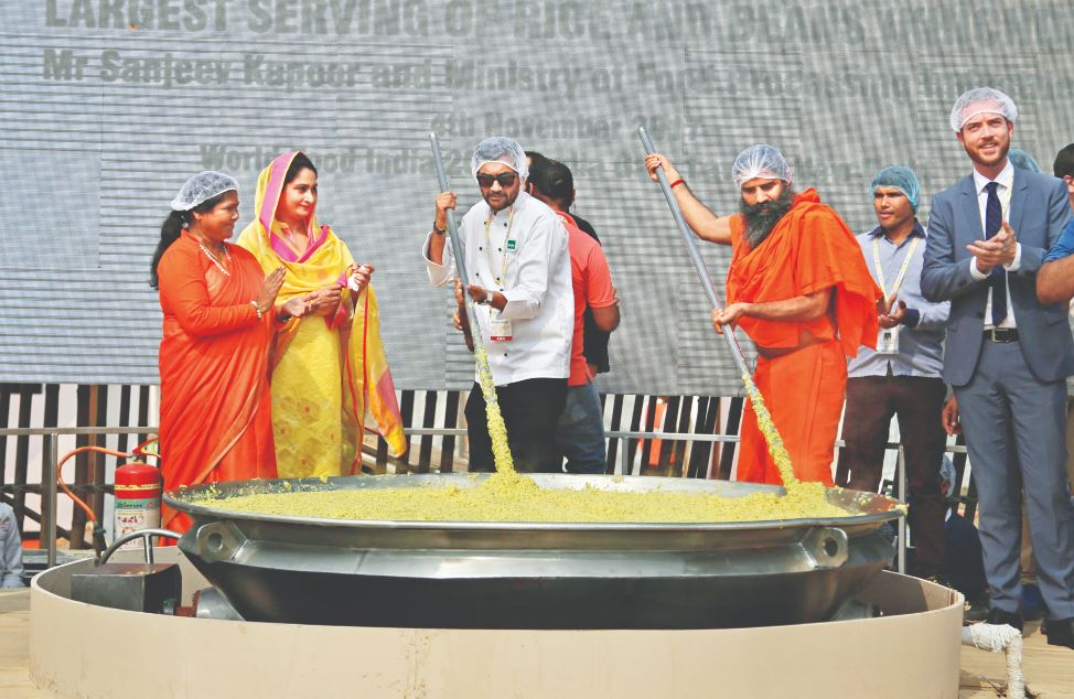 Indian union minister of food processing Harsimrat Kaur Badal, chef Sanjeev Kapoor and Yoga guru Baba Ramdev, preparing the record breaking khichdi at WFI 2017