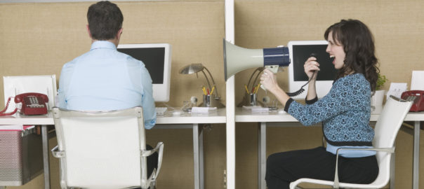 Woman using megaphone to talk to coworker