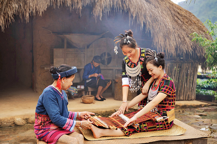 Women busy making handicrafts at the Binglanggu-Hainan Li and Mao Cultural Park