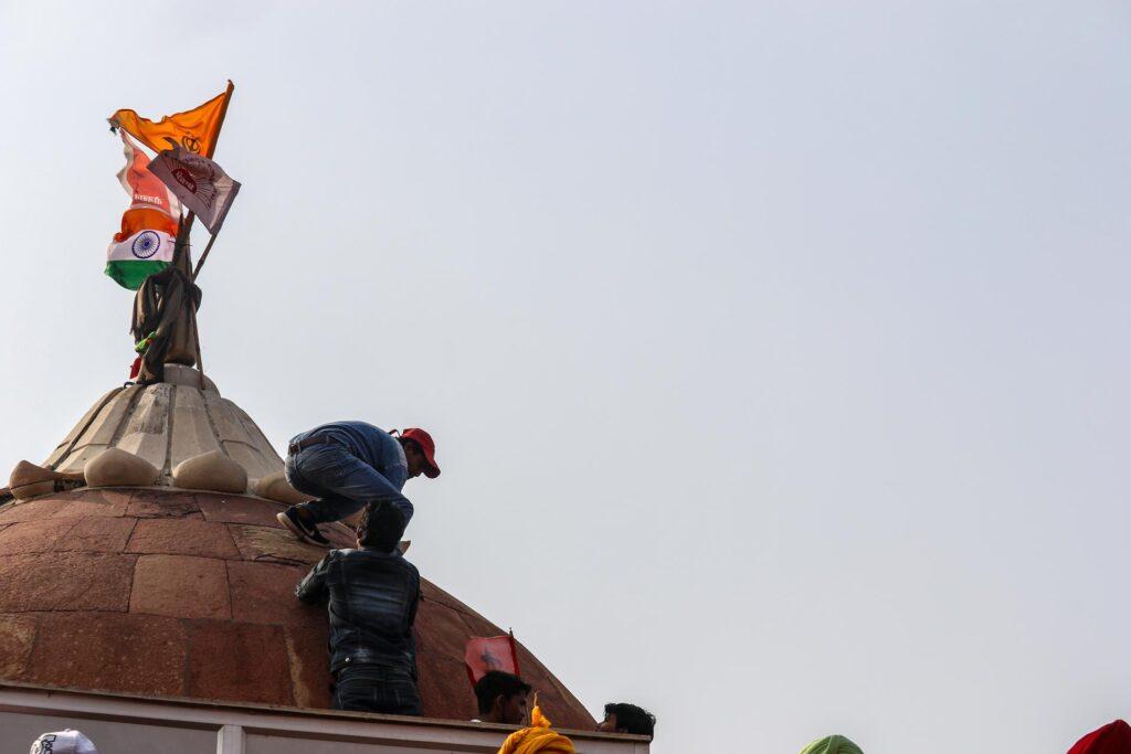 protestor hoist flag at red fort